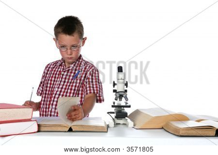 Child Scientist In Glasses Consulting His Books