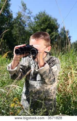 Young Boy In Camoflage In A Field Looking Through Binoculars