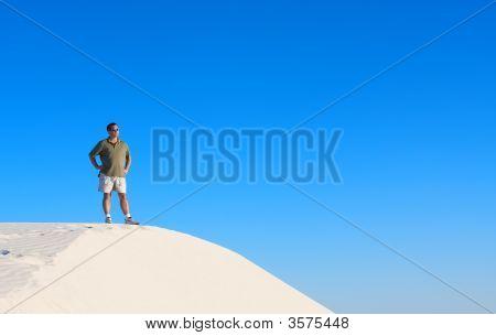 A Man Atop A Sand Dune