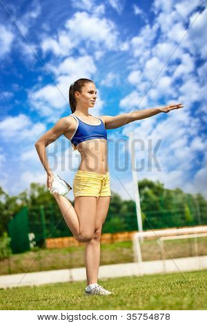Young athletic woman starching legs