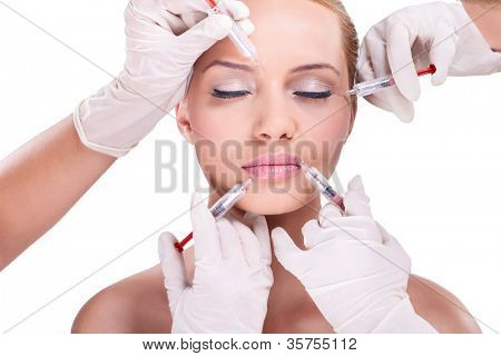 Plastic surgeons giving injection of