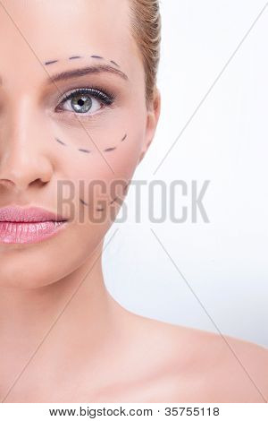 Lines on an attractive Caucasian lady face as marks for cosmetic plastic surgery