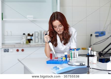 Young female lab technician work with pipette and some tubes, lab shot