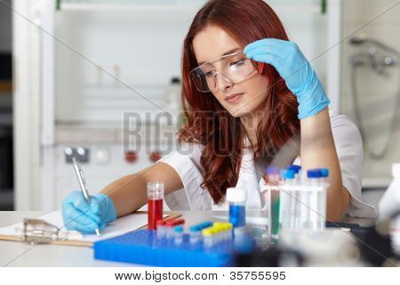 Young female lab technician works on some samples and make notes on her clipboard