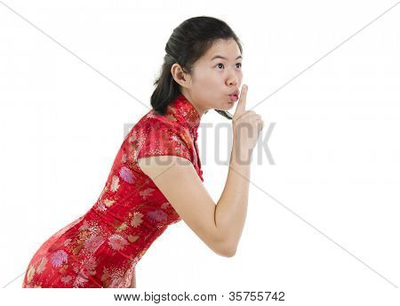 Asian female woman gesturing quiet sign, finger on lips over white background