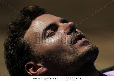 Man laying on long chiar taking the sun