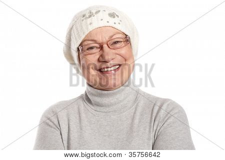 Portrait of happy elderly lady smiling in cap and polo-neck sweater.