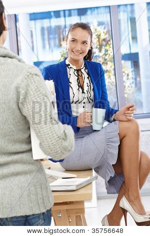 Attractive office girl enjoying coffee break chatting to coworker, sitting on desk with coffee mug handheld.