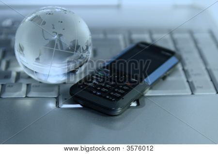 Cellular And Glass Globe On Laptop.