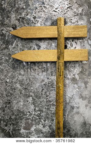 Two wooden blank placards pointing left pinned to a post against a stone wall