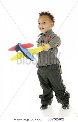 An adorable preschooler in military garb happily playing with a toy airplane.  On a white background.