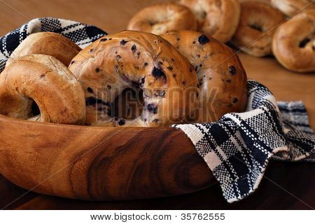 Still life of assorted bagels (blueberry, whole wheat, and cinnamon) in wooden bowl with handwoven cloth.  Additional bagels in soft focus in background.  Closeup with shallow dof.