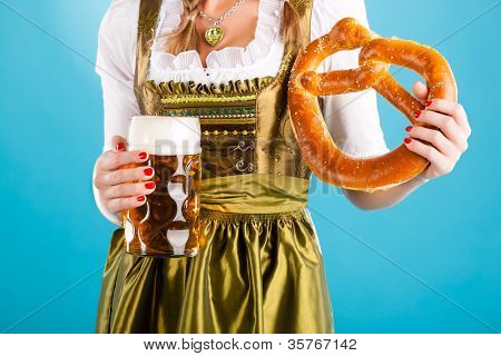 Young woman in traditional Bavarian clothes - dirndl or tracht with a beer stein and beer and pretzel