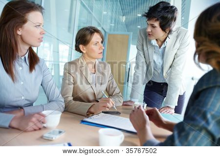 Image of four successful businesswomen interacting at meeting