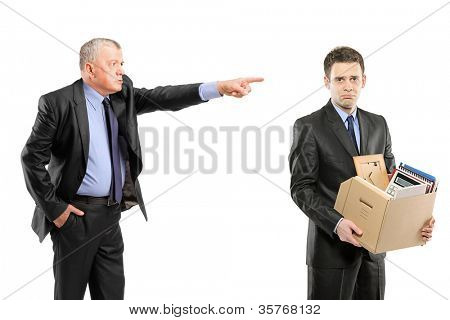 An angry boss firing a man carrying a box of personal items isolated on white background