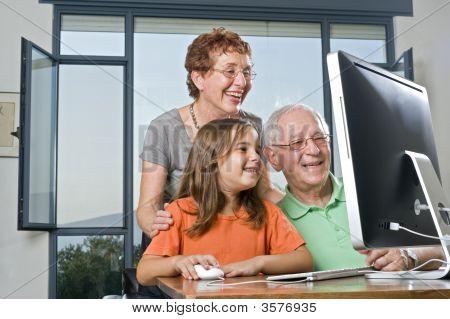 Großeltern und Enkelin mit computer
