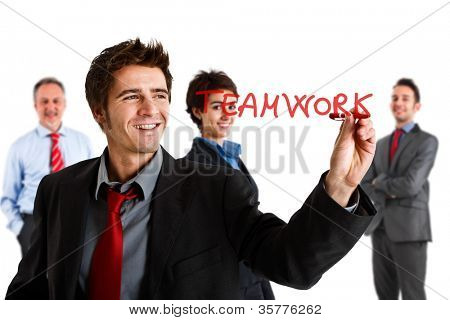 Friendly businessman writing the word Teamwork on the screen
