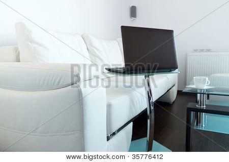 moderne Wohnzimmer mit weißen Ledersofa und laptop