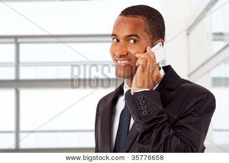 Empresario afroamericano sonriente en el teléfono en su oficina