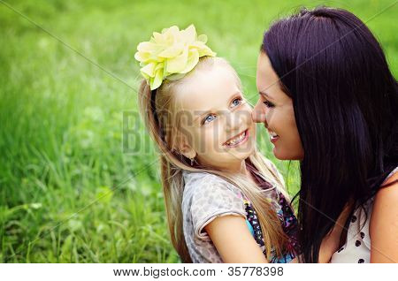 Beautiful young mother with her five years old daughter playing on the grass