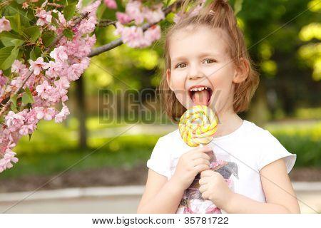 happy little girl licks sweet candy nature summer outdoor