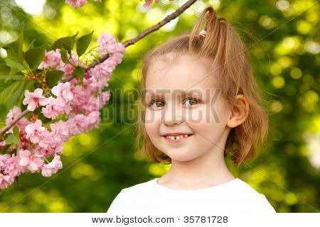 portrait of happy little girl near Japanese cherry tree nature spring outdoor