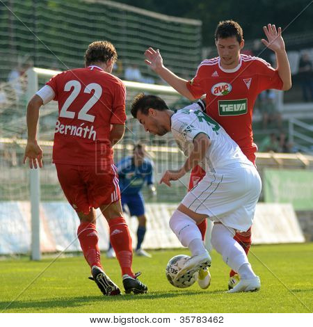 KAPOSVAR, HUNGARY - AUGUST 4: Csaba Bernath (L) in action at a Hungarian National Championship soccer game Kaposvar (white) vs Debrecen (red) August 4, 2012 in Kaposvar, Hungary.