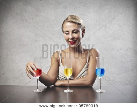 Smiling beautiful woman choosing a drink from three glasses