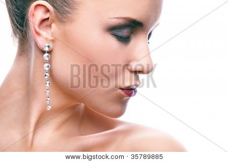 Gorgeous woman with long earrings on white background