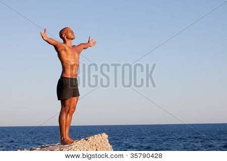 summer man with arms outstretched on vacation