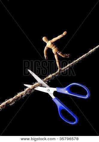 Schere schneiden das Seil an einem Seiltänzer.
