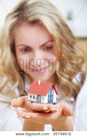 Feliz mulher loira segurando a pequena casa em suas mãos