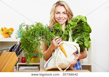 Happy attractive woman standing in kitchen with vegetables in shopping bag