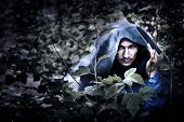 stock photo of dracula  - Mystery man in a raincoat with a hood hiding in the trees - JPG