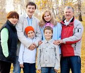Families with children and grandparents in autumn park