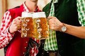 picture of stein  - Two young men in traditional Bavarian Tracht in restaurant or pub with beer and beer stein - JPG