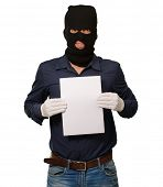 Man wearing a robber mask showing a blank paper on white background