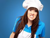 stock photo of berserk  - portrait of a female chef clenching on blue background - JPG