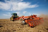 picture of plowed field  - Tractor at work on farm general rural scene