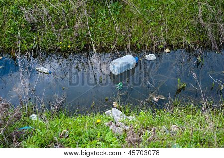 Concept or conceptual unhygienic polluted river,sewage or dirty water and grass with waste,trash and dump background