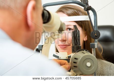 Optometrist checking eye of young woman with a slit lamp