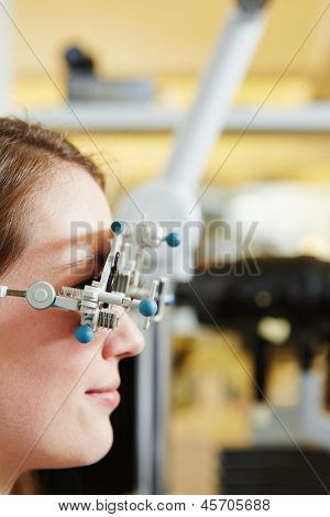 Young woman with trial frame for lens determination at optician