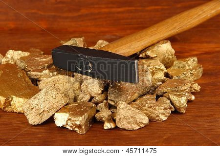 Golden nuggets with hummer on wooden background