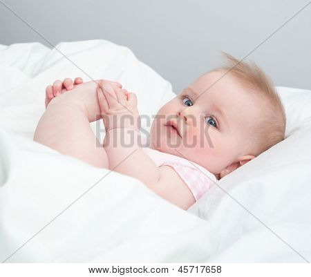 baby playing with his feet on the bed at home