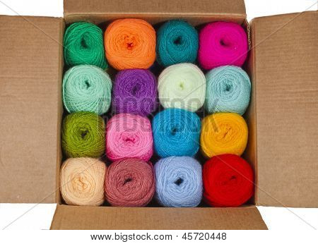 multicolored balls of wool knitting yarn in a cardboard box  isolated on white background