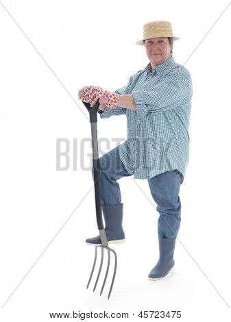 Senior woman gardener wearing straw hat and rubber boots posing with forks over white background