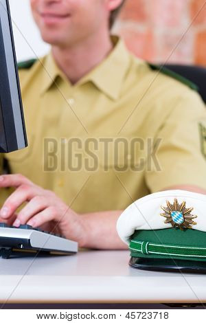 Police officer in police station working on the computer, on a case or registering a complaint
