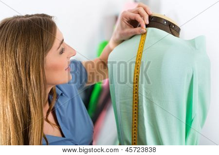 Freelancer - Fashion designer or Tailor working on a design or draft, she takes measure on a dressmakers dummy