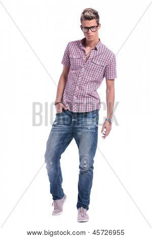 full length picture of a casual young man standing with a hand in his pocket and looking at the camera. on white background