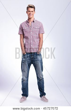 full length photo of a casual young man standing with his hands  in his pockets and smiling to the camera. on background